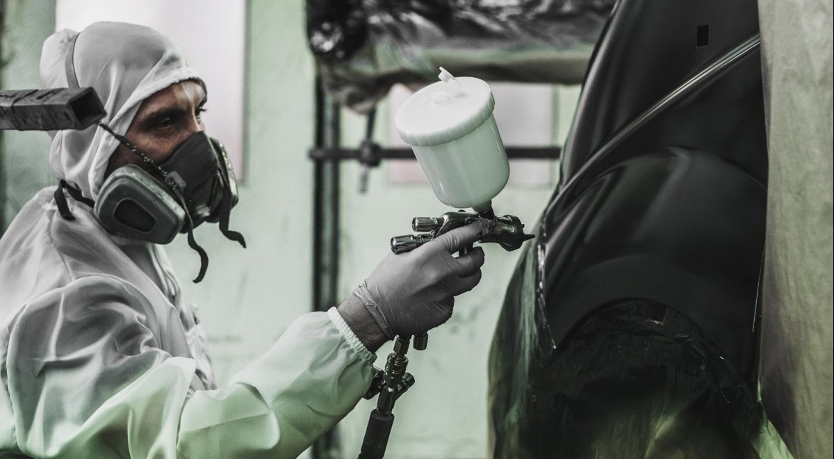 Rzetelny lakiernik nakładający lakier profesjonalnym pistoletem na Krucza 18 w Osielsku obok Bydgoszczy.