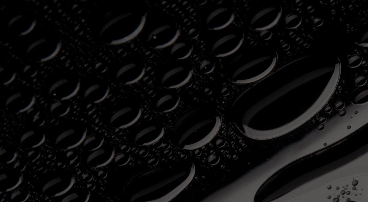 Krople wody na powierzchni czarnego lakieru karoserii.